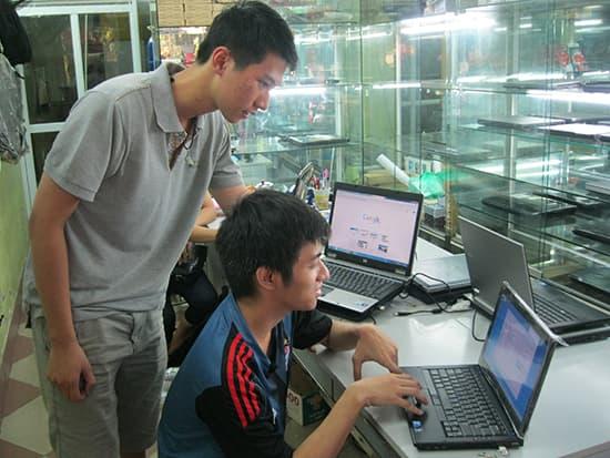 Nhân viên của cửa hàng đang hướng dẫn khách hàng kiểm tra máy